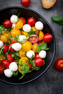 Overhead view of salad with arugula, mozzarella, cherry tomatoes and basil