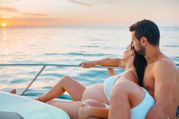 Romantic couple with pregnat woman sitting on boat