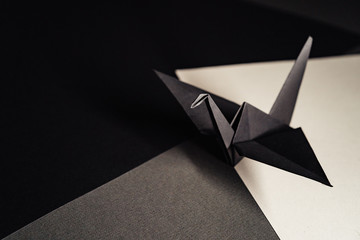 origami crane made of dark gray paper stands on sheets of paper