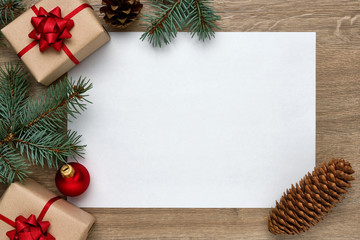 Christmas or New Year background. White sheet of paper with copy space, gift boxes, Christmas balls and Christmas tree branches on wood. Flat lay, top view