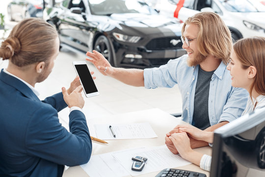 Salesman holding smartphone in hands and showing information to client