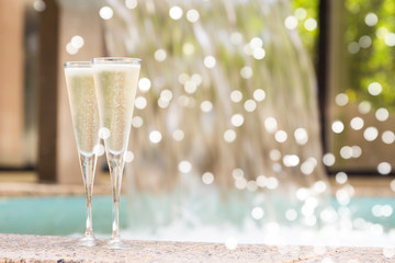 Spoed Foto op Canvas Alcohol Two glasses of champagne near outdoor jacuzzi. Romantic getaway. Valentines background. Horizontal, shallow background with gentle festive holiday bokeh