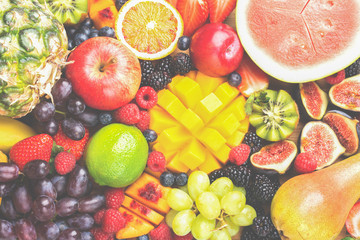 Wall Mural - Healthy raw rainbow fruit background, mango papaya strawberries oranges blueberries pineapple watermelon obn wooden board on light concrete background, top view, selective focus