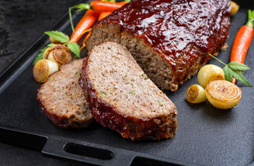 Traditional American meatloaf with ketchup from ground beef with carrots and onion as closeup modern design cast iron tray