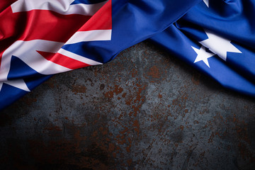 Australia day concept. Australian flag with the text Happy Australia day against a black stone texture background. 26 January.