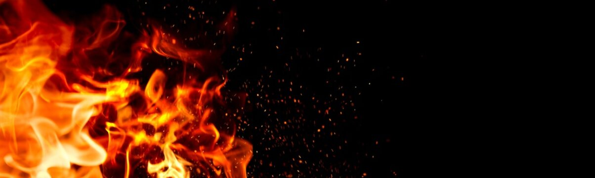 Fire Flame on black background. Flame border close up. Sparks from bonfire over dark night background. Christmas backdrop, wide screen