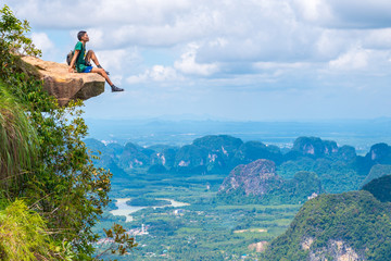 Young traveler sits on a rock that overhangs the abyss, with a beautiful landscape below. Dragon Crest (or Khuan Sai) at Khao Ngon Nak Nature Trail in Krabi, Thailand. Mo Koh Pho Phi National Park.