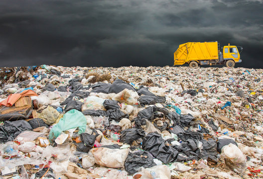 garbage dump pile in trash dump or landfill,truck is dumping the gabage from municipal,garbage dump whit old garbage truck and dark clouds or rain clouds