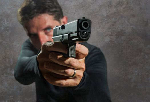 shallow depth of focus action portrait of serious and attractive hitman or special agent man holding gun pointing the weapon isolated on dark background