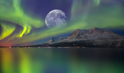 Papiers peints Aurore polaire Northern lights (Aurora borealis) in the sky over Tromso with full moon, Norway