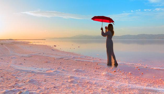 Girl with umbrella in the Maharlu pink lake at sunset - Shiraz, Iran