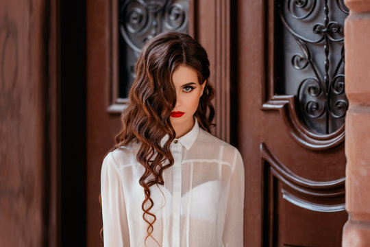portrait of brunette girl. long hair, hairstyle curls waves Hollywood retro style. Delicate makeup, red lips, liner eyeliner. White vintage blouse, brown background. image prom ball graduate, teacher