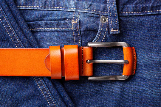 Fashionable leather belt and jeans top view. Leather belt and blue jeans close-up. Belt accessory.