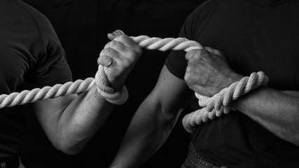 Tug of war. The concept of strength and struggle. Two men are fighting for leadership in tug of war. Men pull a big thick rope.