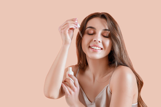 Beautiful young woman applying serum onto her skin against color background