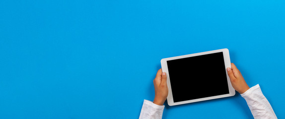 Kid hand holding white tablet computer on light blue background