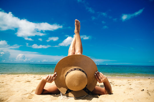 girl in a hat laying on a beach