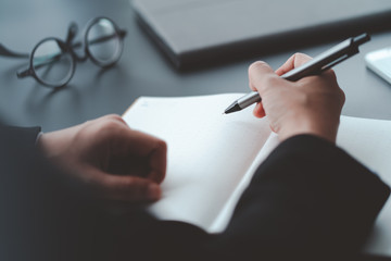 businessman write on notebook on desk in office, conclusion and planning concept