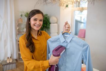 Fototapeta Pleasant positive young woman ironing her shirt obraz