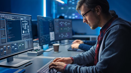 Software Developer Programming, Finding Solutions while Working on Desktop Computers in Data Center System Control Room. Team of Young Professionals Doing High Tech Coding