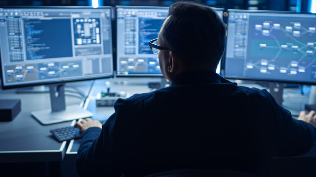 Professional IT Programer Working in Data Center on Desktop Computer with Three Displays, Doing Development of Software and Hardware. Displays Show Blockchain, Data Network Architecture Concept