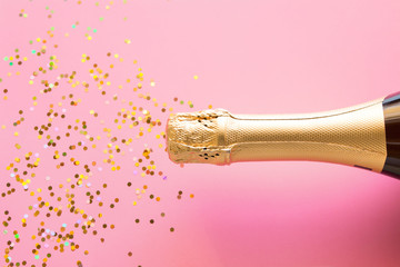 a bottle of champagne and a scattering of confetti. Christmas firecracker concept on pink background