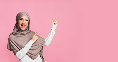 Cheerful muslim woman pointing at copy space on pink background
