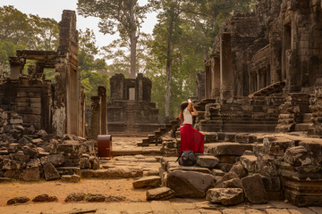 young female tourist in red dress taking a picture of the historic Bayon Temple, Angkor Wat, Cambodia