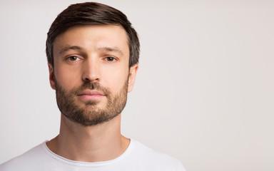 Portrait Of Confident Man Posing Over White Studio Background