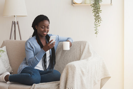 Cheerful black woman using smartphone and drinking coffee on couch