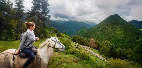 Young woman travels during summer vacation riding horse high in mountains and watches herd of sheep graze against background of beautiful mountains in the province of Tusheti, Georgia country . Fototapete