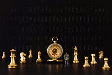 Image of chess game. Businessman looking at compass and pawns, competition, strategy, leadership and success concept