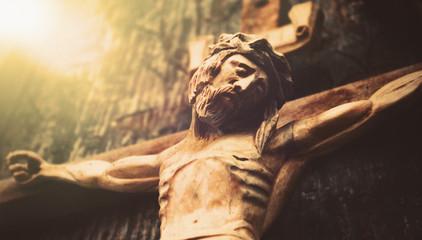 Antique wooden statue of crucified Jesus Christ against dark wooden background