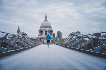 Running in London, Morning run at Millennium Footbridge over the Thames. St Paul's Cathedral in background