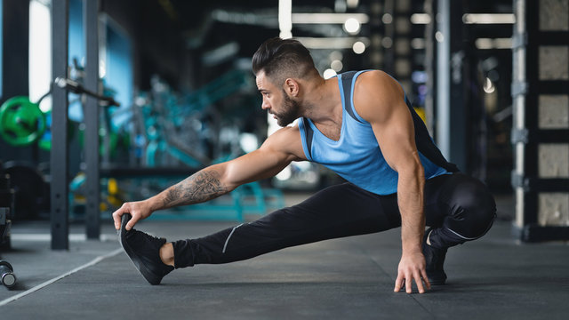 Young athlete stretching legs before training at gym