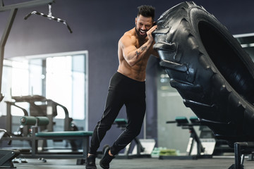 Wall Mural - Muscular man working out in gym flipping big tire