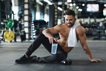 Wall Mural - Muscular guy drinking water, taking break at gym