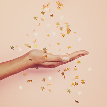 Magical gold confetti stars decoration in female hand on pastel pink background