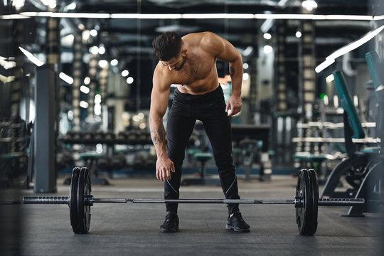 Strong bodybuilder going to exercise with barbells at gym