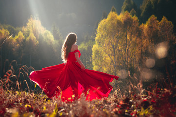 Beautiful brunette girl in a chic red dress posing in the fairy autumn forest.