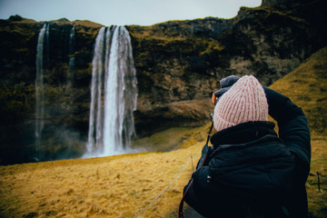 Woman take a picture for Seljalandfoss waterfall on Seljalandsa river, Iceland, Europe.