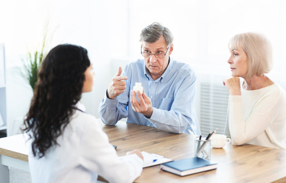 Elderly couple asking doctor how to use pill
