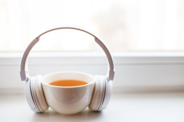 Poster de jardin The white headphones with a cup of tea on the window. headphones on a notebook for notes on a white background