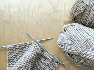 Top view of the process of hand knitting with beige natural wool  of a warm scarf. Close-up, flat lay, copy space, wooden background