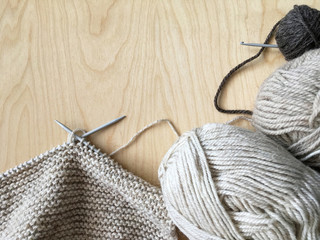 Winter needlework. Hand knitting a warm scarf from beige natural wool yarn. Top view, wooden background, place for textб адфе дфн