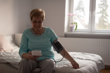 Senior woman checking blood pressure on a monitor