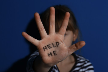Fototapeta Abused little girl showing with phrase HELP ME near blue wall, focus on hand. Domestic violence concept obraz