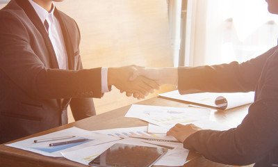 Two confident business man shaking hands during a meeting in the office, success, dealing, greeting and partner concept or team work handshake after meeting completion