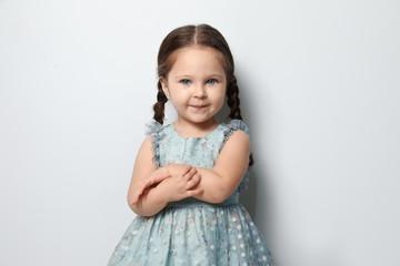 Cute little girl on light grey background Fototapete