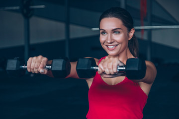 Slim fit muscular brunette woman exercise in gym, lifting weights and doing pilates. Picture with dark evening mood and film color grading.